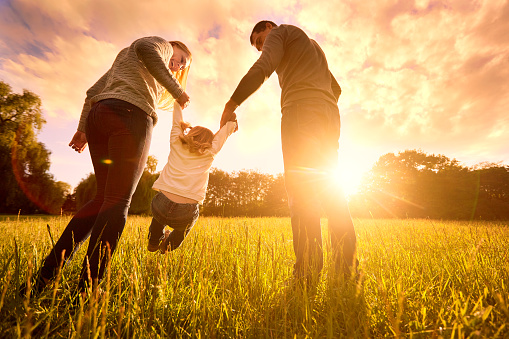 Happy family in the park during evening light
