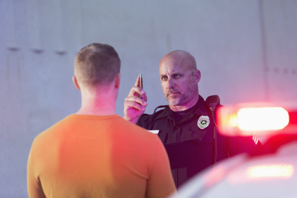 A police officer performs a field sobriety test on a suspected drunk driver